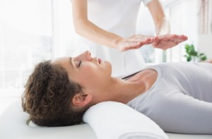 Attractive young woman having reiki treatment in health spa