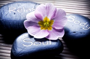 three massage stones - relax, body, soul - and a flower like a c